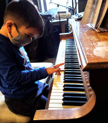 Picture of a young kid playing piano at his piano lesson. Our piano instructors will help you or your kid learn piano with ease.