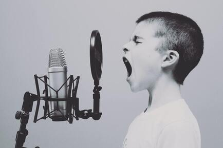 Picture of a kid singing. He clearly takes voice lessons and is singing in a studio. He must have a great voice instructor.